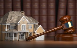 House with gavel and law books.  Real estate law and house auction concept. 3d illustration